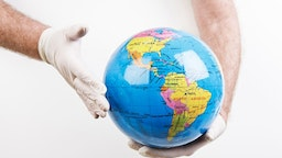Global health | Doctor wearing gloves holds globe - stock photo