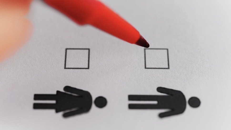 Person marking with pen on male and female gender checklist - stock photo