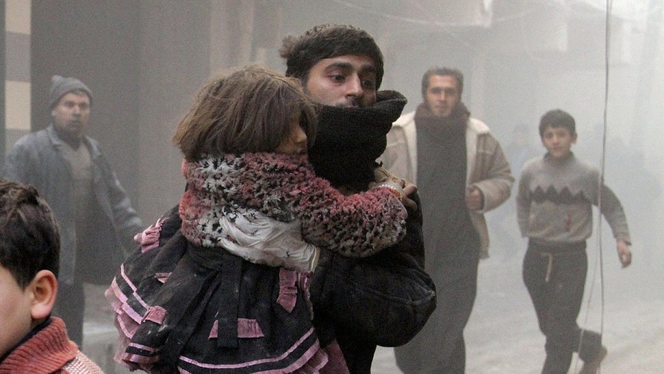 ALEPPO, SYRIA - DECEMBER 23: People are rescued from buildings after Syrian army helicopters dropped 'barrel bombs' on December 23, 2013 in Aleppo, Syria. It has been reported that at least 25 people have been killed, including 6 children, and others injured after the Syrian army dropped bombs on Aleppo, an area within which the Syrian rebels have recently gained territory. (Photo by Salih Mahmud Leyla/Anadolu Agency/Getty Images)