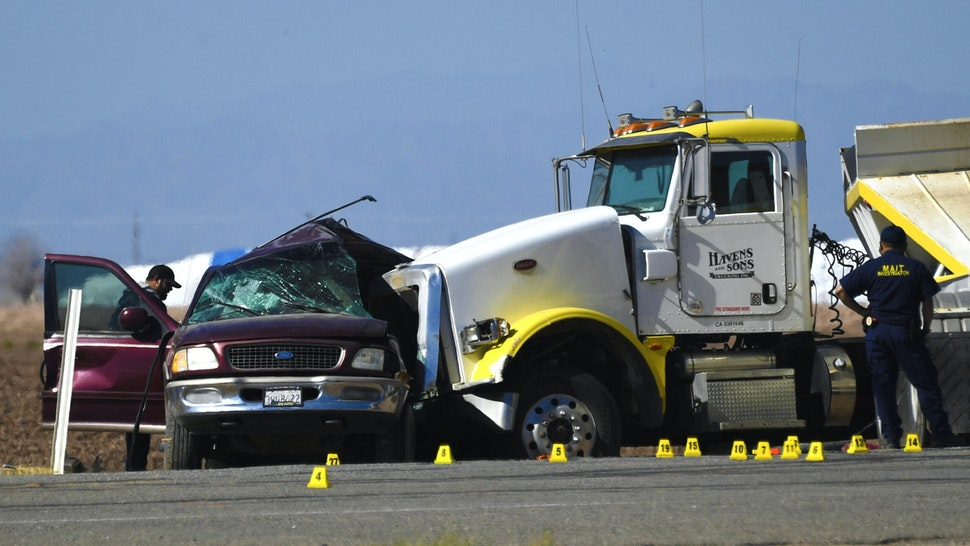 Investigators look over the scene of a crash between an SUV and a semi-truck full of gravel near Holtville, California on March 2, 2021. - At least 13 people were killed in southern California on Tuesday when a vehicle packed with passengers including minors collided with a large truck close to the Mexico border, officials said.