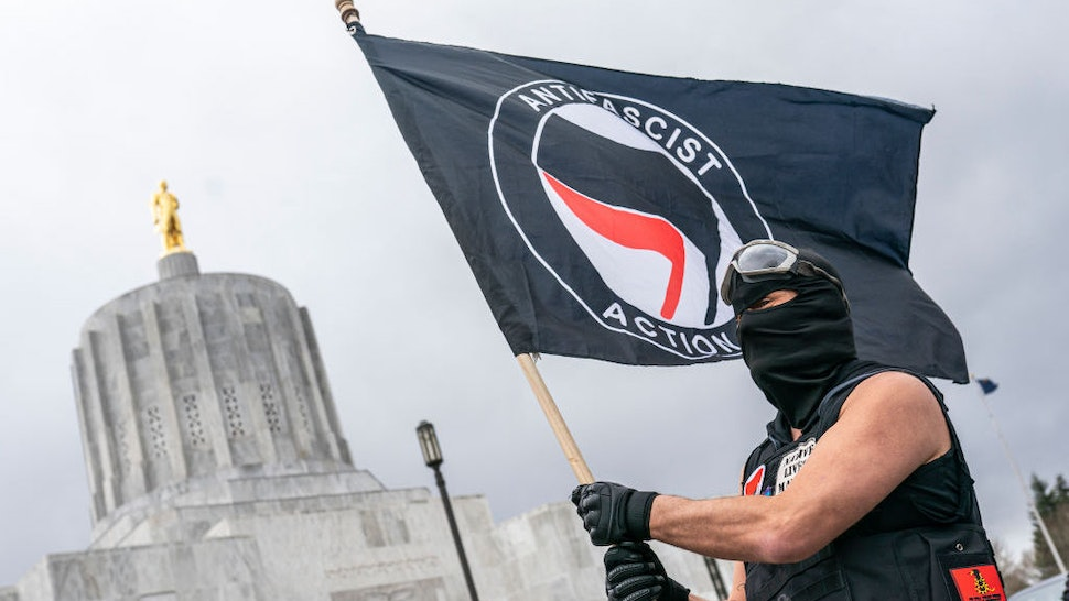 SALEM, OR - MARCH 28: A protester waves an anti-fascist flag at the Oregon statehouse on March 28, 2021 in Salem, Oregon. The protesters clashed with occupants of vehicles that had participated in an American flag-waving car caravan, despite law enforcements efforts to to keep the groups separate. (Photo by Nathan Howard/Getty Images)