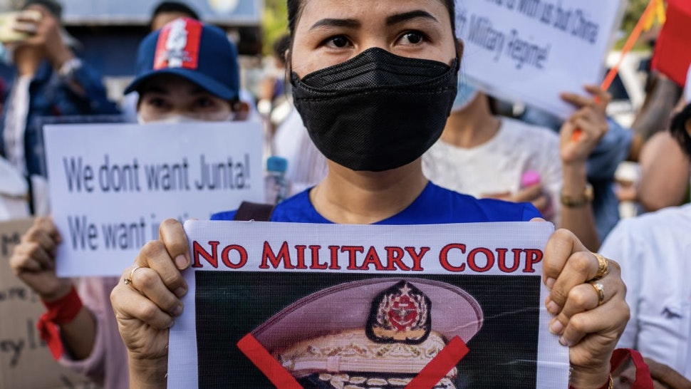 YANGON, MYANMAR - FEBRUARY 12: Protesters hold banners against the military coup and in favor of democracy outside the Russian embassy on February 12, 2021 in Yangon, Myanmar. Myanmar declared martial law in parts of the country, including its two largest cities, as protests continued to draw people to the streets after the country's military junta staged a coup against the elected National League For Democracy (NLD) government and detained de-facto leader Aung San Suu Kyi. The U.S. government imposed sanctions and froze the U.S. assets of several of the coup's leaders and their families. (Photo by Hkun Lat/Getty Images)
