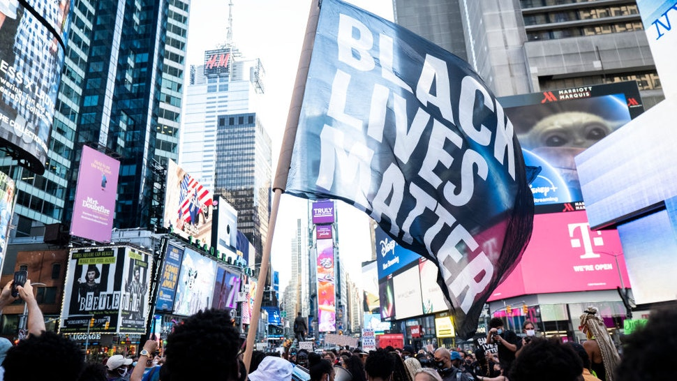 """MANHATTAN, NY - July 26: A protester holds a large flag that says, """"Black Lives Matter"""" which is draping the landscape of Times Square in New York. This non-violent protest was a March for Black Womxn which started at Times Square and walked through Manhattan. This is days after Portland and other cities have seen federal agents have taken protesters and put into unmarked vehicles while others have been beaten and pepper sprayed. Protesters continue taking to the streets across America and around the world after the killing of George Floyd at the hands of a white police officer Derek Chauvin that was kneeling on his neck during for eight minutes, was caught on video and went viral. During his arrest as Floyd pleaded, """"I Can't Breathe"""". The protest are attempting to give a voice to the need for human rights for African American's and to stop police brutality against people of color. They are also protesting deep-seated racism in America. Many people were wearing masks and observing social distancing due to the coronavirus pandemic. Photographed in the Manhattan Borough of New York on July 26, 2020, USA."""