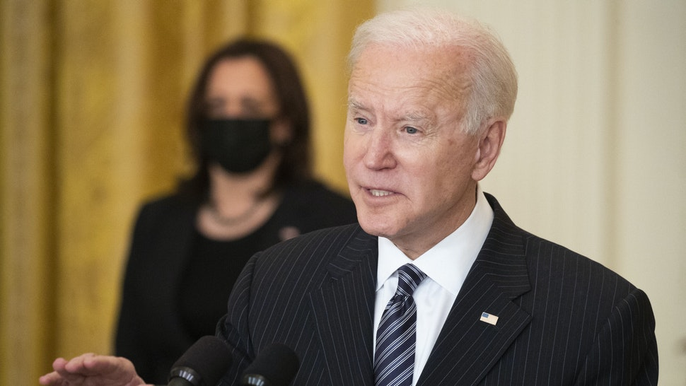 U.S. President Joe Biden speaks while delivering an address as U.S. Vice President Kamala Harris, left, listens in the East Room of the White House in Washington, D.C., U.S., on Thursday, March 18, 2021. Biden announced the U.S. on Friday will clinch his goal of administering 100 million Covid-19 vaccine shots in the first 100 days of his presidency, reaching the mark six weeks ahead of time.