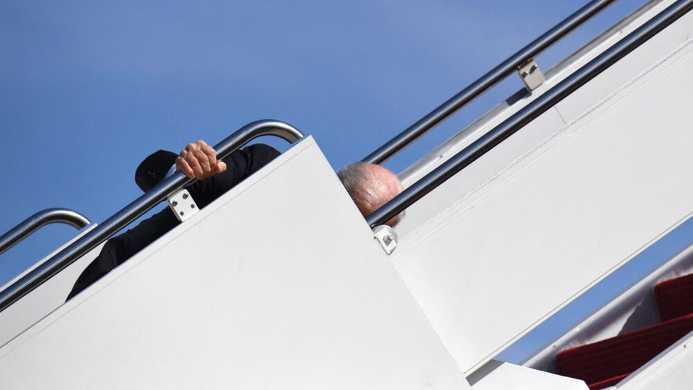TOPSHOT - US President Joe Biden trips as he boards Air Force One at Joint Base Andrews in Maryland on March 18, 2021. - President Biden travels to Atlanta, Georgia, to tour the Centers for Disease Control and Prevention, and to meet with Georgia Asian American leaders, following the Atlanta Spa shootings.