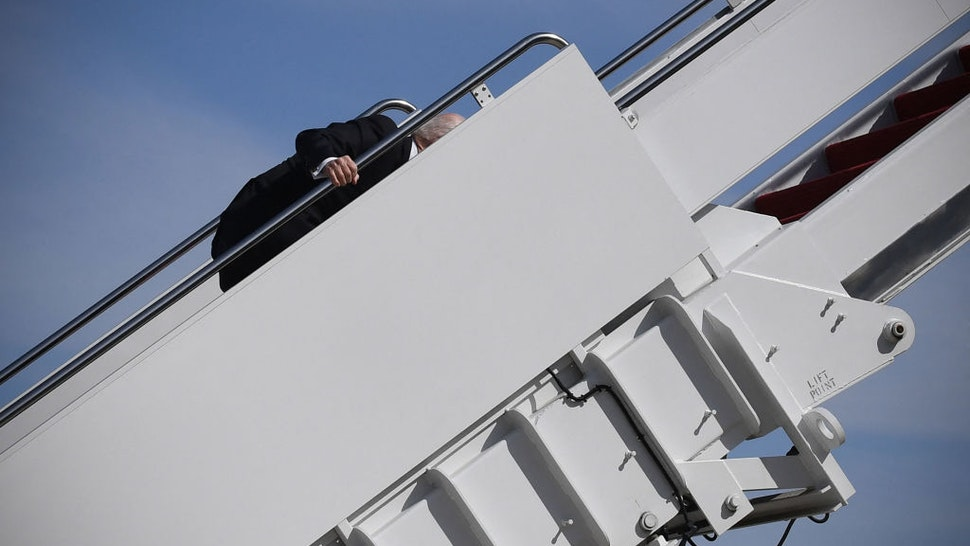 US President Joe Biden trips while boarding Air Force One at Joint Base Andrews in Maryland on March 19, 2021. - President Biden travels to Atlanta, Georgia, to tour the Centers for Disease Control and Prevention, and to meet with Georgia Asian American leaders, following the Atlanta Spa shootings.