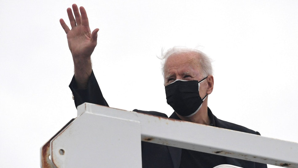 US President Joe Biden waves before boarding Air Force One after spending the weekend in Wilmington, at New Castle airport in New Castle, Delaware on March 28, 2021.