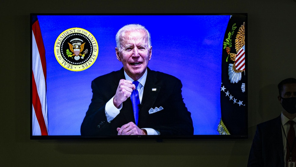 WASHINGTON, DC - MARCH 03: A screen in the auditorium shows President Joe Biden as he participates in a virtual event with members of the House Democratic Caucus from the South Court Auditorium in the Eisenhower Executive Office Building next to the White House on March 3, 2021 in Washington, DC.