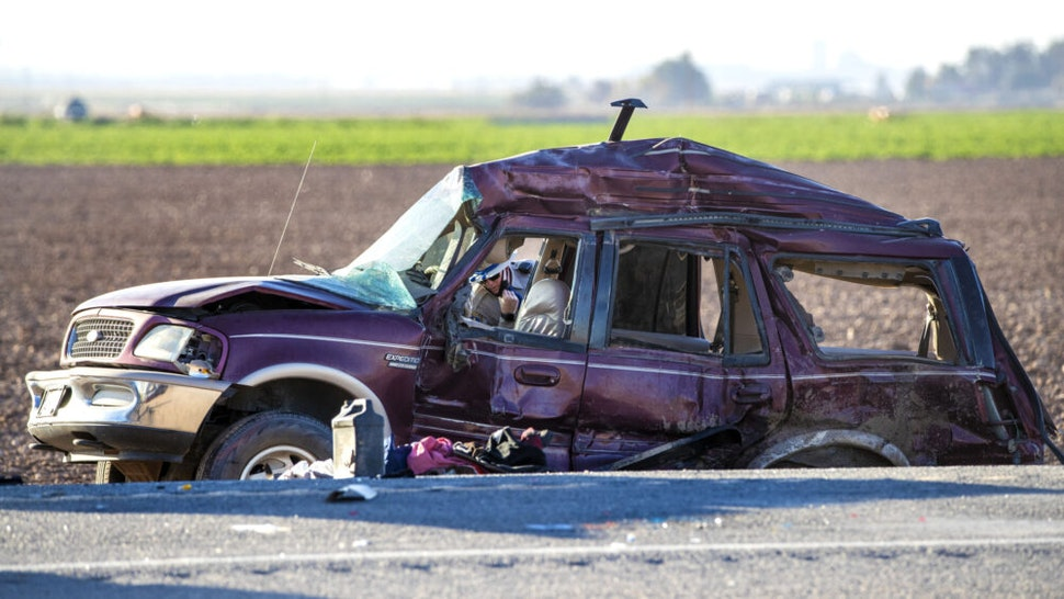 HOLTVILLE, CA - MARCH 2, 2021: A CHP officer looks inside a mangled SUV which was carrying 25 people when it collided with a semi-truck killing 13 on Highway 115 near the Mexican border on March 2, 2021 in Holtville, California. All the back seats had beens stripped form the vehicle. The passengers in the SUV ranged in age form 15-53.