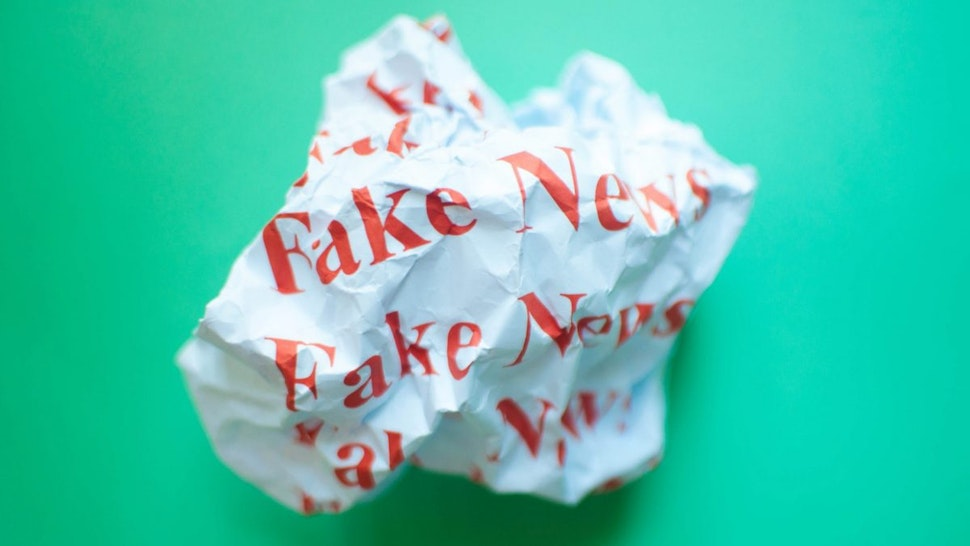 Crumpled paper with red font fake news against blue green background.