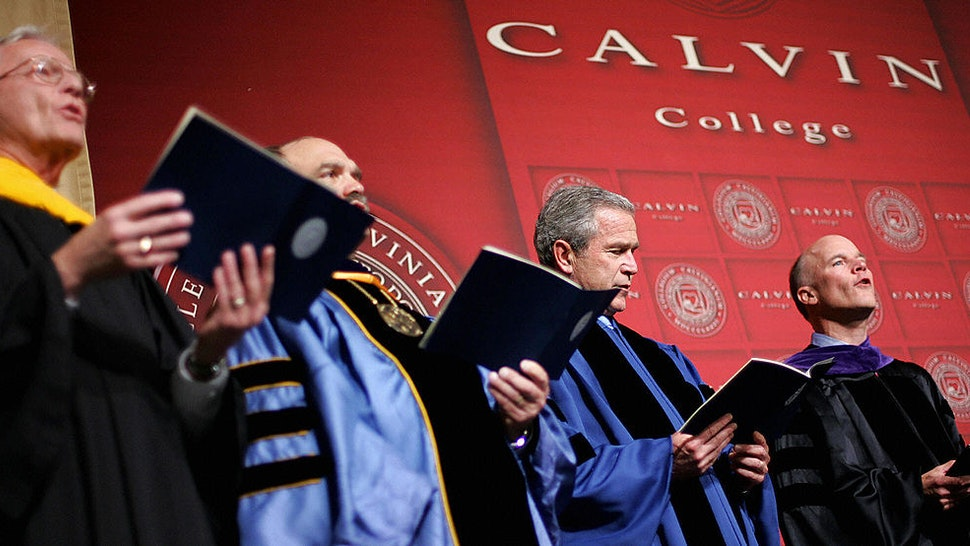 GRAND RAPIDS, UNITED STATES: US President George W. Bush looks at his hymnal while others sing before delivering the commencement address at Calvin College 21 May 2005 in the Calvin College Field House in Grand Rapids, Michigan