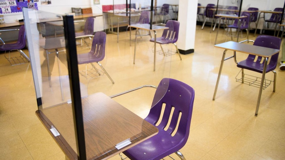 Plexiglass dividers surround desks as students return to in-person learning at St. Anthony Catholic High School during the Covid-19 pandemic on March 24, 2021 in Long Beach, California. - The school of 445 students implemented a hybrid learning model, with approximately 60 percent of students returning to in an in-person classroom learning environment with Covid-19 safety measures including face masks, social distancing, plexiglass barriers around desks, outdoor spaces, and schedule changes.
