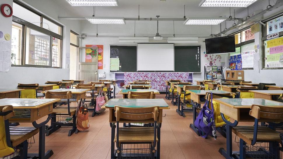 Row of empty desks in front of whiteboard. Interior of classroom in school.