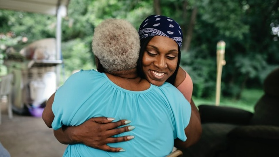 """Young black woman hugging senior family member - stock photo Young black woman hugging senior family member. Family is out doors at a cookout.""""nMembers of a black middle class America family."""