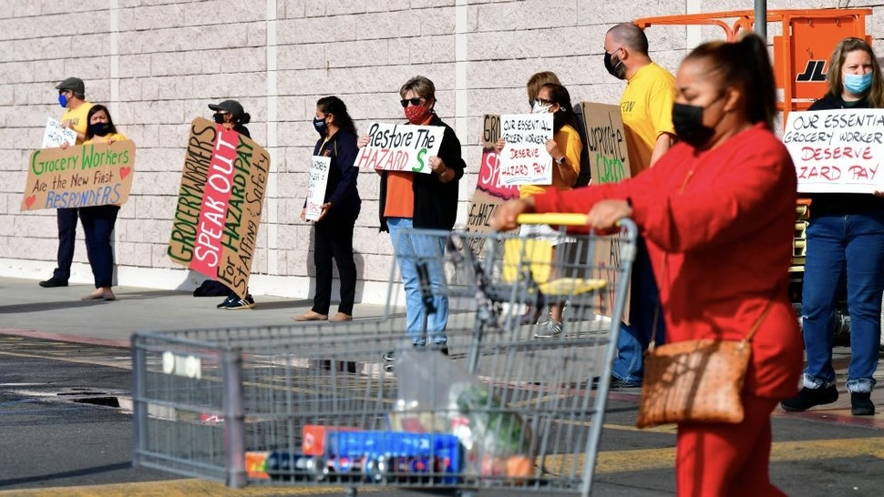 """Supermarket workers hold placards in protest in front of a Food 4 Less supermarket in Long Beach, California on February 3, 2021, after a decision by owner Kroger to close two supermarkets rather than pay workers an additional $4.00 in """"hazard pay"""" for their continued work during the coronavirus pandemic. - Kroger, which owns Ralphs and food 4 Less, said it will close one of each store in April after the Long Beach city council passed a law mandating """"hazard pay"""" for grocery store workers. Long Beach was the first city in the region to approve a hazard pay ordinance. (Photo by Frederic J. BROWN / AFP) (Photo by FREDERIC J. BROWN/AFP via Getty Images)"""