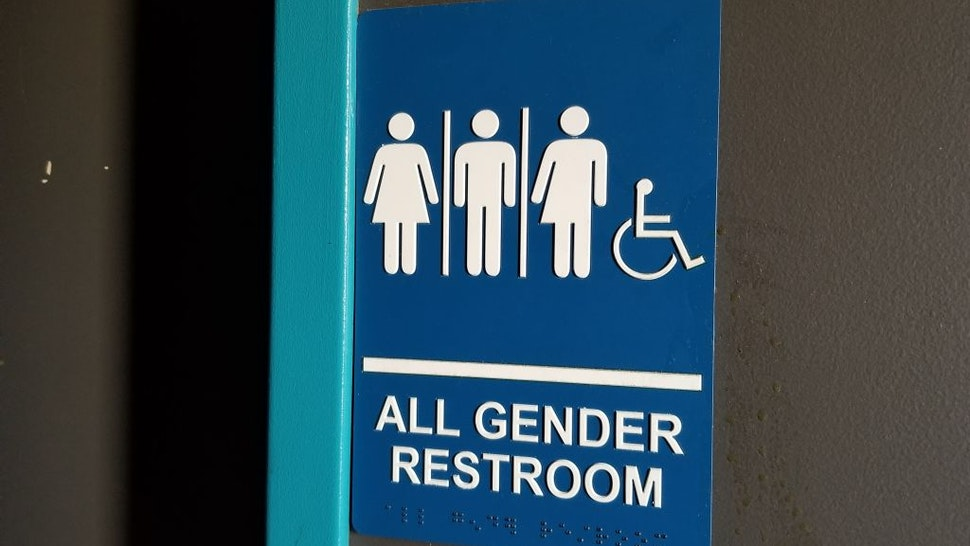 Close-up of sign for all gender restroom in Dublin, California, with male, female and gender-inclusive stick figure illustrations, March 13, 2019.