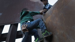TIJUANA, MEXICO - DECEMBER 02: A boy is hoisted by fellow members of the migrant caravan over the U.S.-Mexico border fence on December 2, 2018 from Tijuana, Mexico. Numerous members of the caravan were able to cross over from Tijuana to San Diego and were quickly taken into custody by U.S. Border Patrol agents. Most had planned to request political asylum in the United States after traveling more than 6 weeks from Central America. (Photo by John Moore/Getty Images)