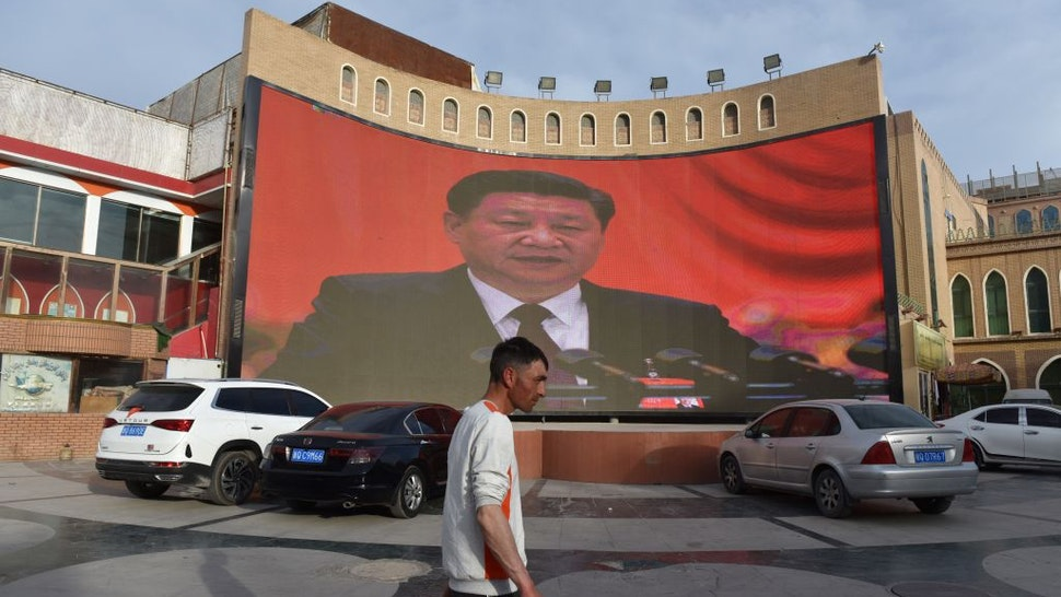 """This photo taken on June 4, 2019 shows a man walking past a screen showing images of China's President Xi Jinping in Kashgar in China's northwest Xinjiang region. - China has enforced a massive security crackdown in Xinjiang, where more than one million ethnic Uighurs and other mostly Muslim minorities are believed to be held in a network of internment camps that Beijing describes as """"vocational education centres"""" aimed at steering people away from religious extremism. (Photo by Greg Baker / AFP) (Photo credit should read GREG BAKER/AFP via Getty Images)"""