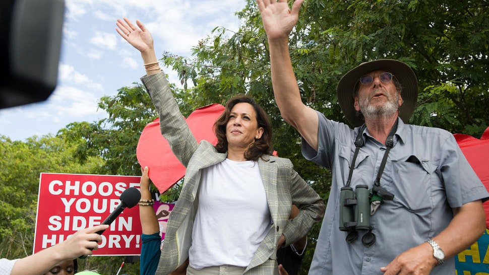 HOMESTEAD, FLORIDA - JUNE 28: Democratic Presidential candidate, Sen. Kamala Harris (D-CA) waves to children as she stands on a ladder to see over a fence into the grounds of a detention center for migrant children on June 28, 2019 in Homestead, Florida. Democratic presidential candidates visited the detention center, which is the nation's largest center for detaining immigrant children, as the candidates spend time in the Miami area after participating in a nationally televised debate. (Photo by Joe Raedle/Getty Images)