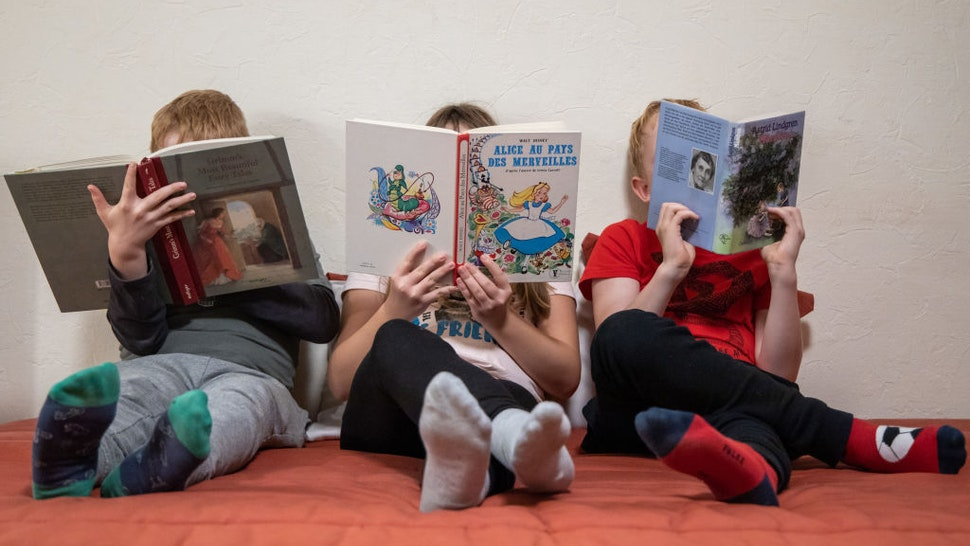 """04 November 2019, France (France), Grosbliederstorff: ILLUSTRATION - Three children each read an English (l), a French (M) and a German book. (to dpa """"The book is dead - or not?"""") Photo: Daniel Karmann/dpa"""