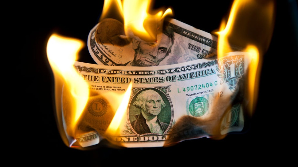 Burning US five and one dollar bills, London, 8th August 2011.