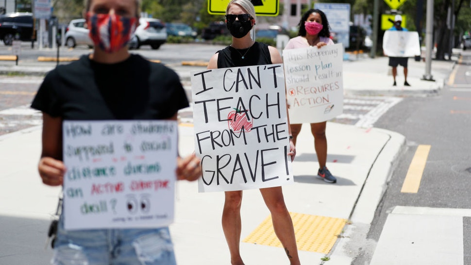 TAMPA, FL - JULY 16: Middle school teacher Brittany Myers, (C) stands in protest in front of the Hillsborough County Schools District Office on July 16, 2020 in Tampa, Florida. Teachers and administrators from Hillsborough County Schools rallied against the reopening of schools due to health and safety concerns amid the COVID-19 pandemic.