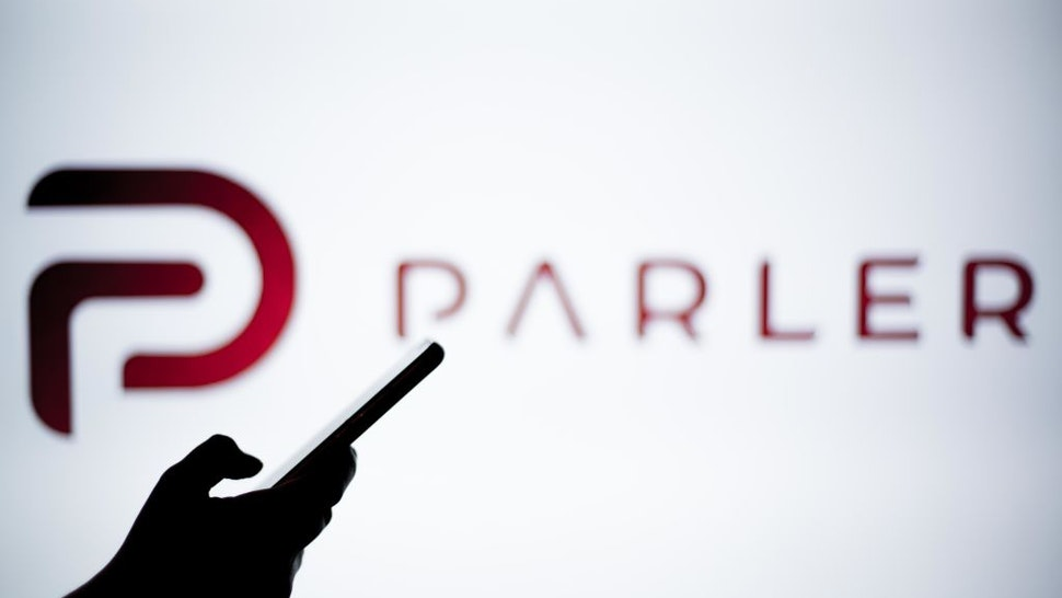 SPAIN - 2021/01/14: In this photo illustration a Parler logo is seen behind a smartphone. The 'free speech' social media platform, Parler, a hit with Trump supporters and an alternative to Twitter, stops working after losing support from Amazon, Apple and Google.