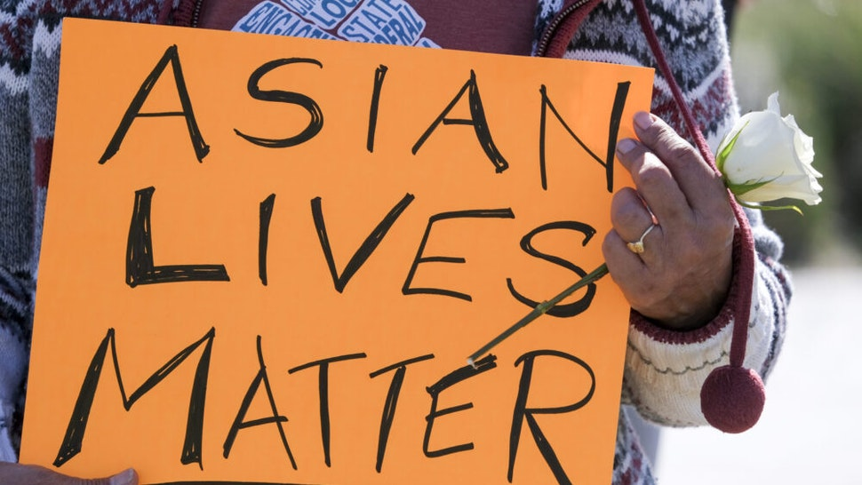 A demonstrator holding a sign and a flower takes part in a rally to raise awareness of anti-Asian violence, near Chinatown in Los Angeles, California, on February 20, 2021. - The rally was organized in response to last month's fatal assault of Vicha Ratanapakdee, an 84-year-old immigrant from Thailand, in San Francisco.