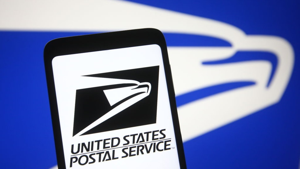 In this photo illustration the United States Postal Service (USPS) logo is seen on a smartphone and a pc screen.