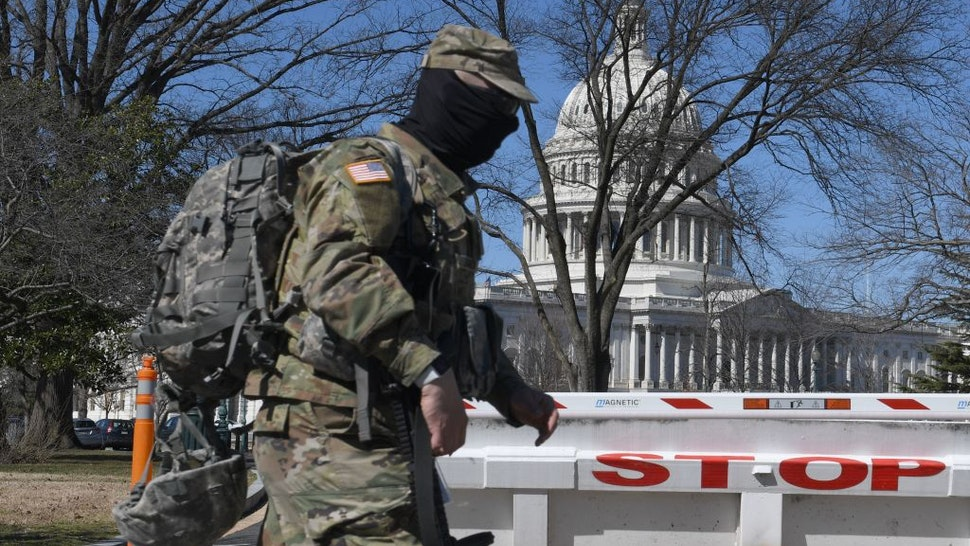 A members of the National Guard walks near the US Capitol Building on Capitol Hill March 3, 2021, in Washington, DC.