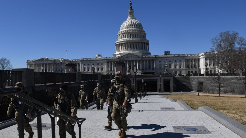 Members of the National Guard walk near the US Capitol Building on Capitol Hill March 3, 2021, in Washington, DC.