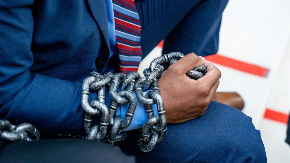 ATLANTA, GA - MARCH 08: Demonstrators wear chains while holding a sit-in inside of the Capitol building in opposition of House Bill 531 on March 8, 2021 in Atlanta, Georgia. HB531 will restrict early voting hours, remove drop boxes, and require the use of a government ID when voting by mail.