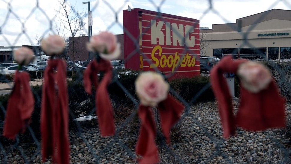 """Flowers hang from the perimeter fence outside a King Soopers grocery store in Boulder, Colorado, on March 23, 2021, one day after a mass shooting left ten dead, including a Boulder police officer. - Colorado police on Tuesday said a 21-year-old man has been charged with 10 counts of murder, a day after a mass shooting at a grocery store in the city of Boulder. """"This suspect has been identified as Ahmad Alissa, 21,"""" Boulder Police Chief Maris Herold told a news conference. (Photo by Jason Connolly / AFP) (Photo by JASON CONNOLLY/AFP via Getty Images)"""