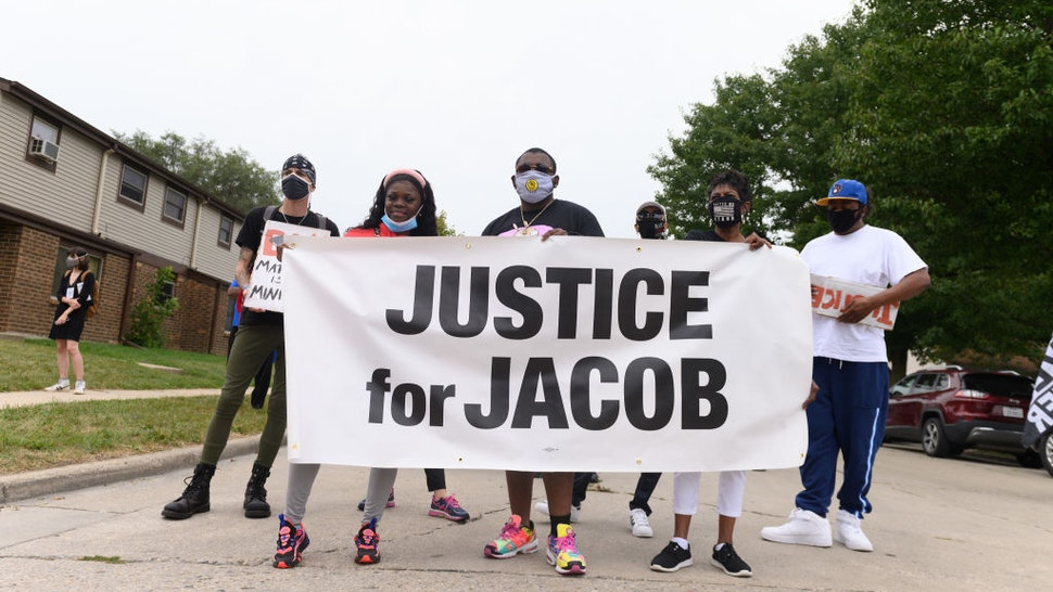 """Protesters hold a banner during a community celebration and call for justice for Jacob Blake as grassroots group MoveOn flies an airplane banner and drives a mobile billboard calling on voters to """"Reject Trump's Violence,"""" in response to Donald Trump's visit on September 01, 2020 in Kenosha, Wisconsin."""