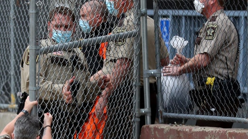 A law enforcement officer goes down while opening a gate for fired Minneapolis police officer Derek Chauvin as fellow officers escorted Chaurin from the rear of the Family Justice Center after a motion hearing Friday in Minneapolis.