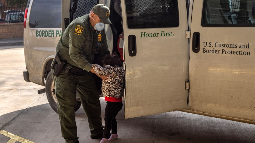 BROWNSVILLE, TEXAS - FEBRUARY 25: A U.S. Border Patrol agent releases a young asylum seeker with her family at a bus station on February 25, 2021 in Brownsville, Texas. U.S. immigration authorities are now releasing asylum seeking families after they cross the U.S.-Mexico border and taken into custody. The immigrant families are then free to travel to destinations throughout the U.S. while awaiting asylum hearings. (Photo by John Moore/Getty Images)