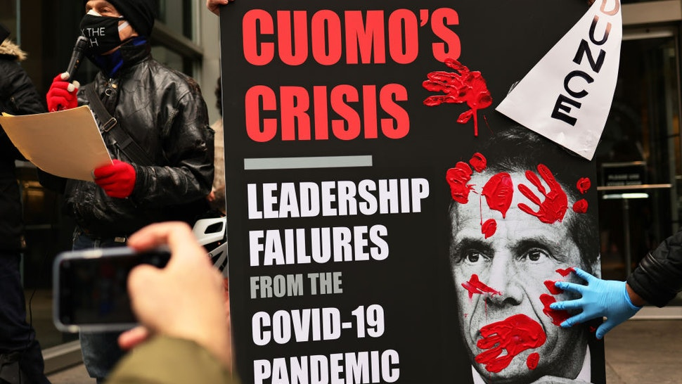 A person places his red painted hands on a poster of Gov. Andrew Cuomo's book as people gather outside of his NYC office to protest against cuts to health care on March 01, 2021 in New York City.