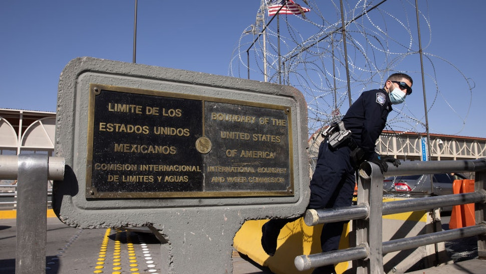 CIUDAD JUAREZ, MEXICO - MARCH 16: A U.S. Customs and Border Protection officer awaits immigrants crossing into the United States on March 16, 2021 in Ciudad Juarez, Mexico. Some 50 asylum seekers crossed the Santa Fe International Bridge from Mexico as part of the Biden administration's unwinding of the Trump-era Migrant Protection Protocols, (MPP), also known as the 'Remain in Mexico' immigration policy. Many of the asylum seekers, most from Central America, had been waiting in Mexico for more than a year. The immigrants are now free to travel to destinations within the United States pending asylum court hearings. (Photo by John Moore/Getty Images)