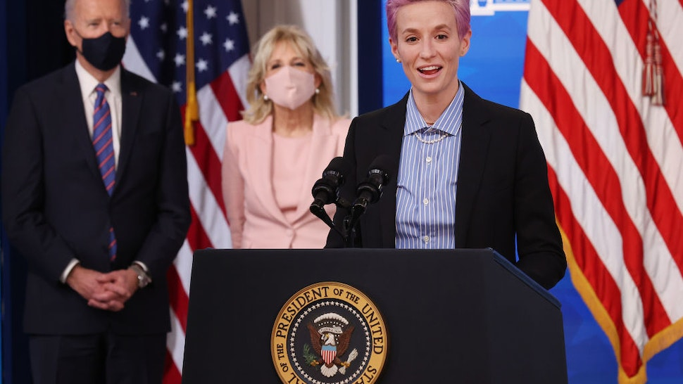 Olympic gold medalist and two-time World Cup champion soccer player Megan Rapinoe deliers remarks during and event to mark Equal Pay Day with U.S. President Joe Biden (L) and first lady Dr. Jill Biden in the South Court Auditorium in the Eisenhower Executive Office Building on March 24, 2021 in Washington, DC.