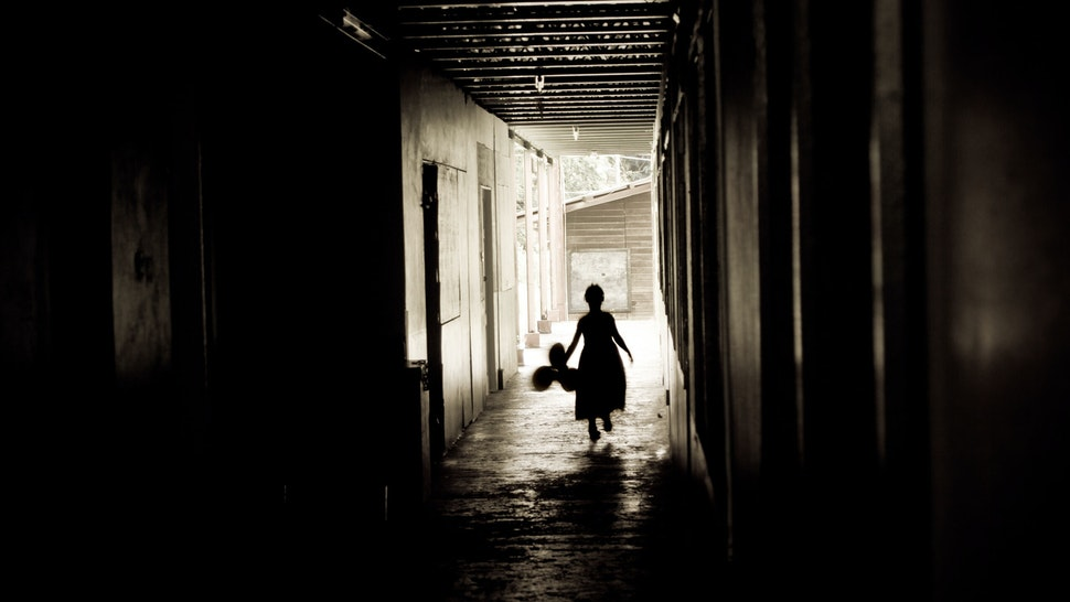 little girl silhouette in dirty alley with balloons - stock photo