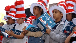 """HOLLYWOOD - MARCH 11: Children read from """"The Cat in the Hat"""" book at a ceremony honoring the late children's book author Dr. Seuss (Theodore Geisel) with a star on the Hollywood Walk of Fame on March 11, 2004 in Hollywood , California. (Photo by Vince Bucci/Getty Images)"""