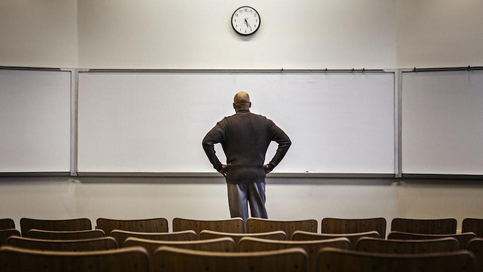 Professor standing in empty classroom - stock photo