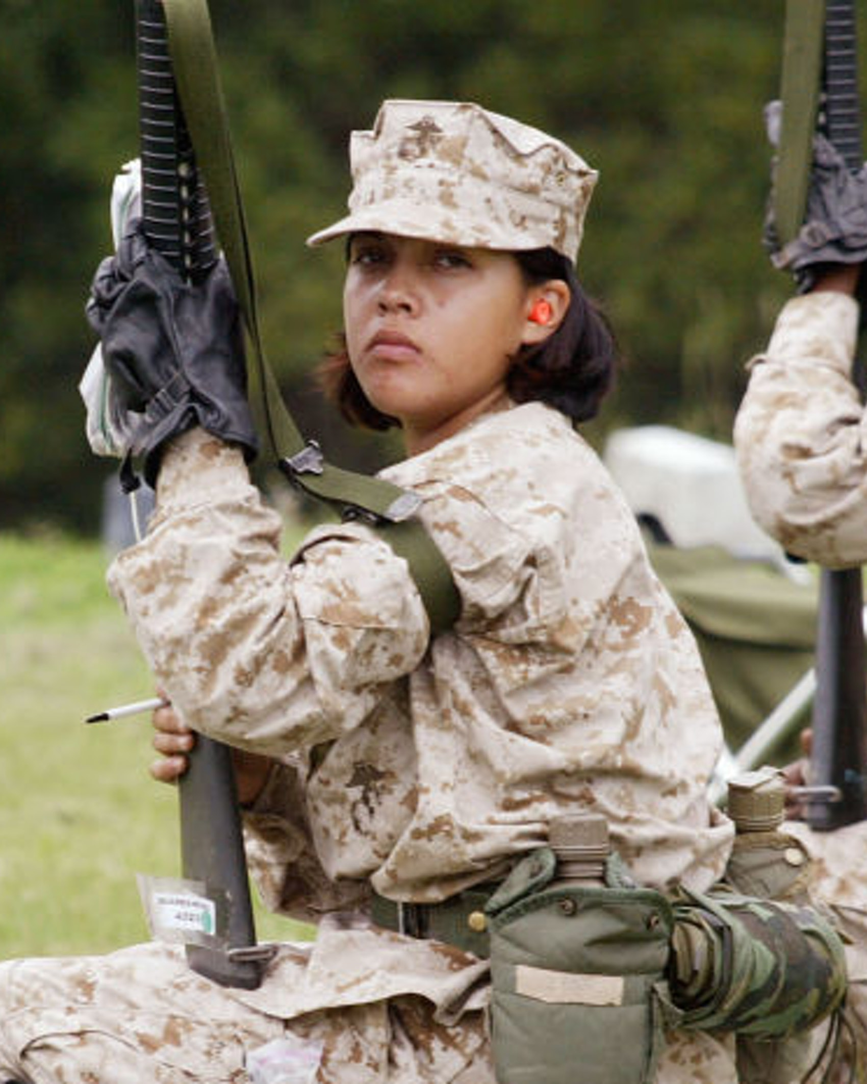 PARRIS ISLAND, SC - JUNE 21: Female Marine Corps recruits wait for a turn to shoot on the rifle range at the United States Marine Corps recruit depot June 21, 2004 in Parris Island, South Carolina. Marine Corps boot camp, with its combination of strict discipline and exhaustive physical training, is considered the most rigorous of the armed forces recruit training. Congress is currently considering bills that could increase the size of the Marine Corps and the Army to help meet US military demands in Iraq and Afghanistan. (Photo by Scott Olson/Getty Images)