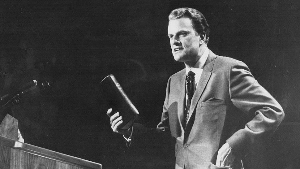 American evangelist Billy Graham, giving a speech on stage, circa 1970.