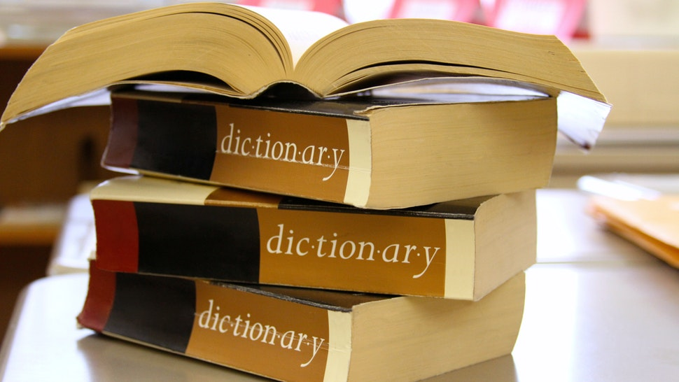 Stack of dictionaries on a desk - stock photo