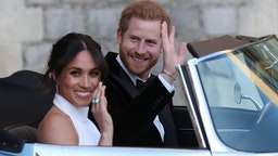 WINDSOR, UNITED KINGDOM - MAY 19: Duchess of Sussex and Prince Harry, Duke of Sussex wave as they leave Windsor Castle after their wedding to attend an evening reception at Frogmore House, hosted by the Prince of Wales on May 19, 2018 in Windsor, England.