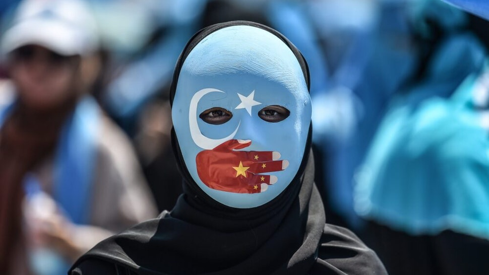 TOPSHOT - A demonstrator wearing a mask painted with the colours of the flag of East Turkestan and a hand bearing the colours of the Chinese flag attends a protest of supporters of the mostly Muslim Uighur minority and Turkish nationalists to denounce China's treatment of ethnic Uighur Muslims during a deadly riot in July 2009 in Urumqi, in front of the Chinese consulate in Istanbul, on July 5, 2018. - Nearly 200 people died during a series of violent riots that broke out on July 5, 2009 over several days in Urumqi, the capital city of the Xinjiang Uyghur Autonomous Region, in northwestern China, between Uyghurs and Han people.