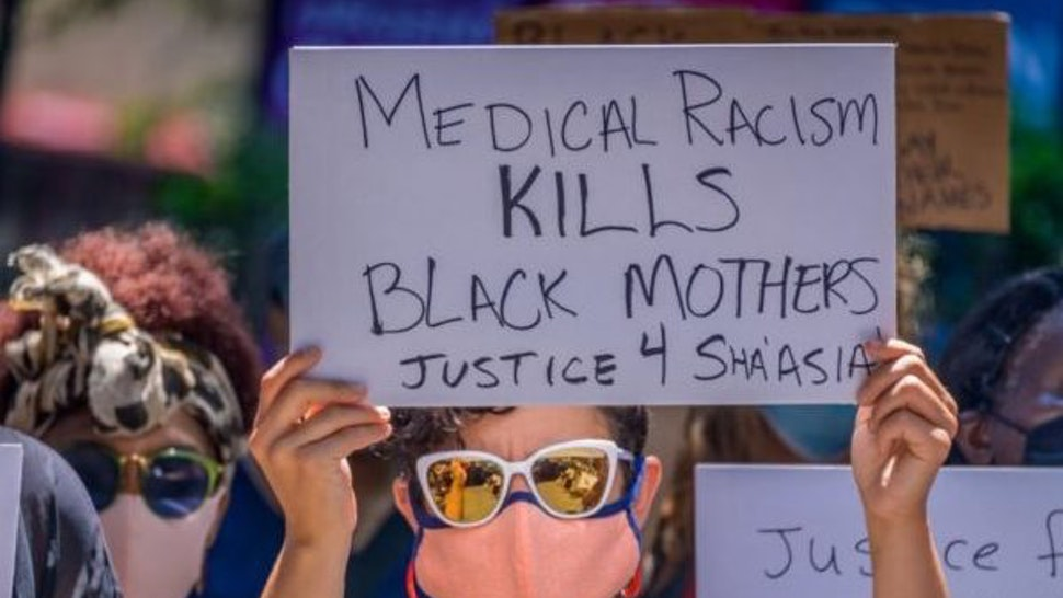 BROOKLYN, NEW YORK, UNITED STATES - 2020/07/09: Participant holding a sign at the rally. Family members, activists and concerned citizens gathered outside Woodhull Hospital holding a rally to demand justice for Sha-Asia Washington, a 26-year-old Black New Yorker, who died on July 3 during childbirth at a the Brooklyn hospital. (Photo by Erik McGregor/LightRocket via Getty Images)