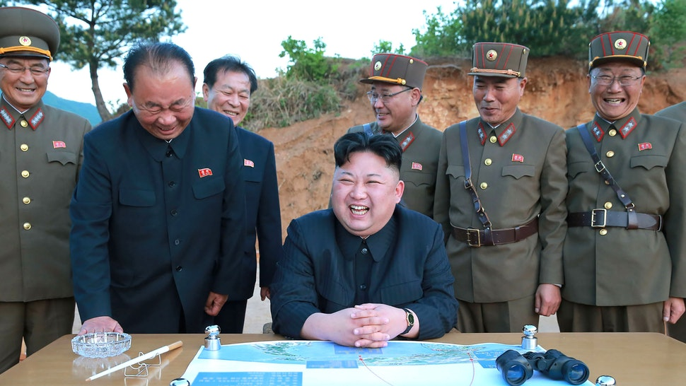 This picture taken on May 14, 2017 and released from North Korea's official Korean Central News Agency (KCNA) on May 15 shows North Korean leader Kim Jong-Un (C) reacting during a test launch of a ground-to-ground medium long-range strategic ballistic rocket Hwasong-12 at an undisclosed location.