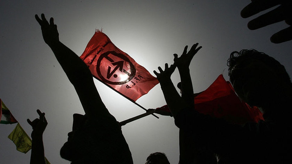 Supporters of the Popular Front for the Liberation Palestine hold up the PFLP red flag as they demonstrate at the Palestinian parliament in Gaza City 14 March 2006. Protests broke out across the West Bank and Gaza Strip as Israeli troops stormed a prison compound in the West Bank town of Jericho in a vast operation to arrest jailed militant Ahmed Saadat, the leader of the leftist Popular Front for the Liberation of Palestine and his three comrades held over the assassination in 2001of far-right Israeli tourism minister Rehavam Zeevi. A Palestinian security guard was killed and 18 others wounded in the Israeli attack. AFP PHOTO/MOHAMMED ABED (Photo credit should read MOHAMMED ABED/AFP via Getty Images)